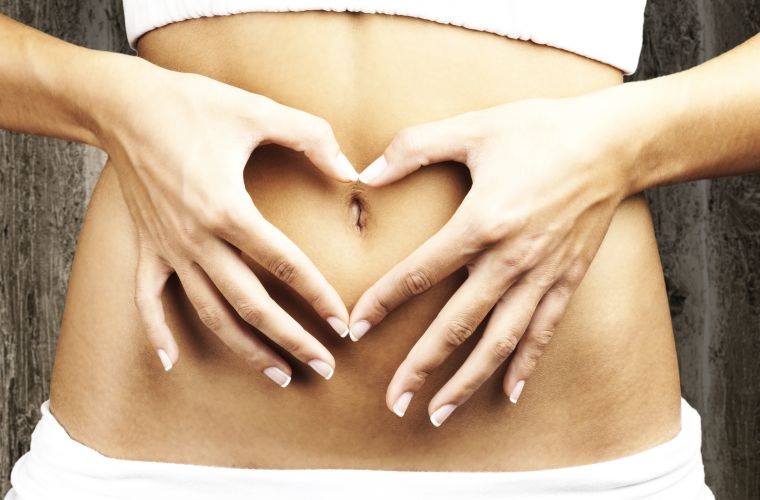 Woman making heart shape with hands over her stomach