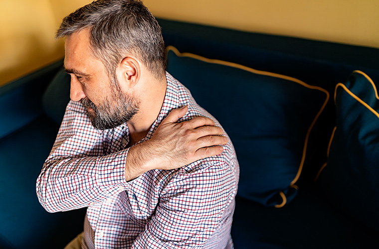 Man holding onto sore shoulder